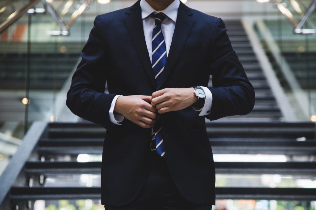 Blauer Anzug mit blau-gestreifter Krawatte