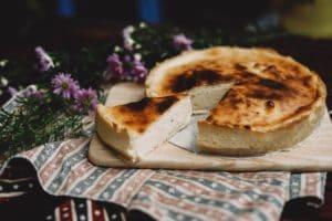 Käsekuchen, veganer Käsekuchen, Cheesecake, Kuchen auf Brett, Lieblingsrezept, Nachtisch, Süßspeise, lila Blumen